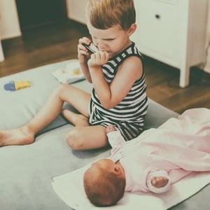 Esikoisesta voi tuntua, ettei häntä rakasteta enää tai että äiti on aina vauvan kanssa. Kuva: iStockphoto