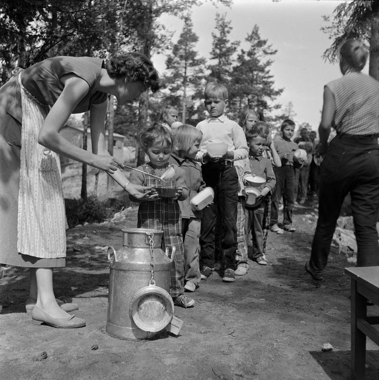 Nainen jakoi ruokaa lapsille Herttoniemen leikkipuistossa vuonna 1950. (Kuvan lähde: helsinkikuvia.fi)